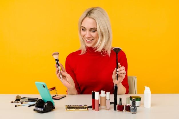 Blogger donna caucasica che presenta prodotti di bellezza e trasmette in diretta