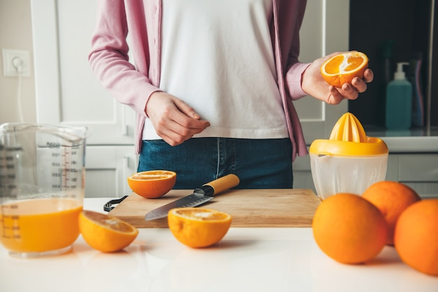 La donna caucasica in abiti casual sta affettando la frutta e facendo il succo a casa in cucina