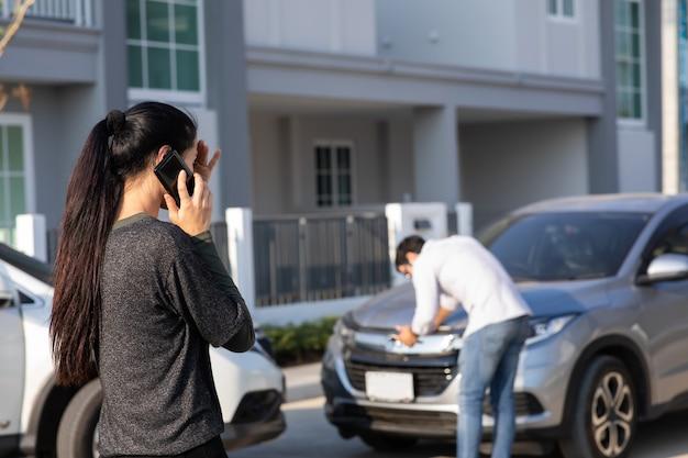 Driver della donna caucasica che fa telefonata all'agente di assicurazione dopo incidente stradale. incidente. assicurazione auto un concetto di assicurazione contro i danni.
