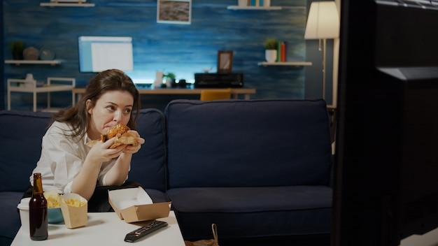 Donna caucasica che mangia hamburger dalla borsa delle consegne