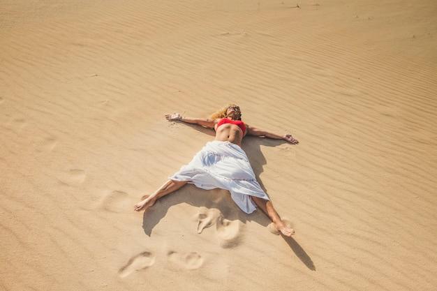 Donna caucasica godendo sulle dune di sabbia con un bagno di sole