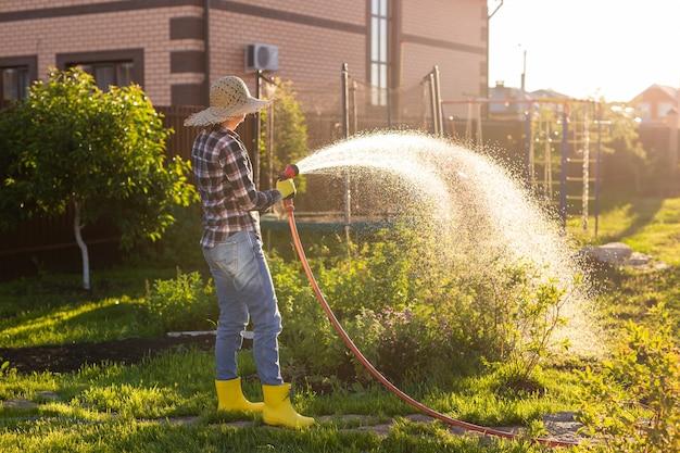 Giardiniere della donna caucasica in abiti da lavoro che innaffia i letti nel suo orto sulla soleggiata giornata estiva calda. concetto di lavoro in giardino e nella tua fattoria