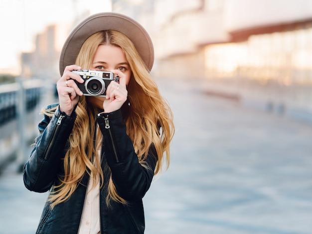 Donna caucasica in cappello utilizzando la fotocamera all'aperto