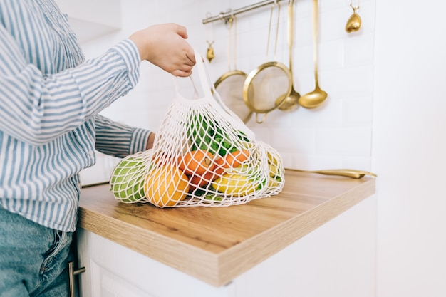 Donna caucasica tenere borsa a rete eco con verdure fresche nella cucina moderna.