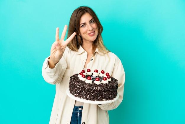 Donna caucasica che tiene la torta di compleanno isolata su sfondo blu felice e conta tre con le dita