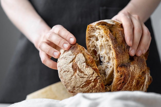 Donna caucasica che tiene il pane fresco dal forno, cuoce il pane fatto in casa, pane a lievitazione naturale prodotti deliziosi e naturali, cottura di cibi sani, ciabatta di pasticceria