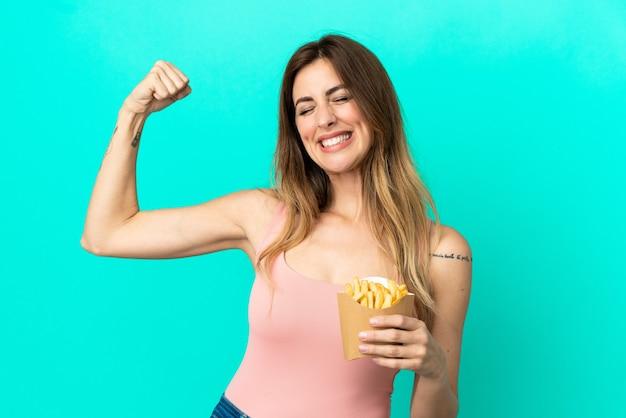 Donna caucasica che tiene patatine fritte isolate su sfondo blu facendo un gesto forte