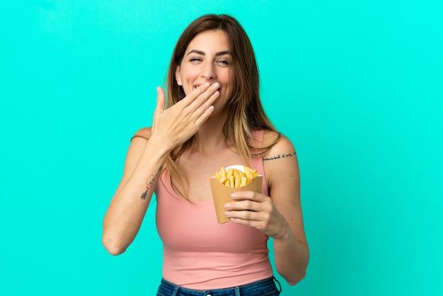 Donna caucasica che tiene patatine fritte isolate su sfondo blu felice e sorridente che copre la bocca con la mano