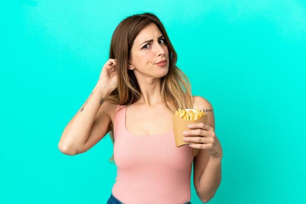Donna caucasica che tiene patatine fritte isolate su sfondo blu avendo dubbi?