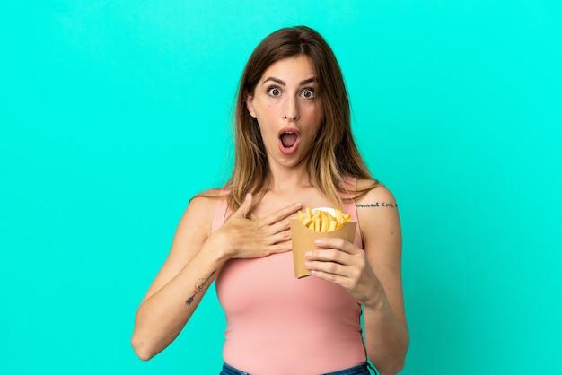 Donna caucasica che tiene patatine fritte isolate su sfondo blu sorpresa e scioccata mentre guarda a destra