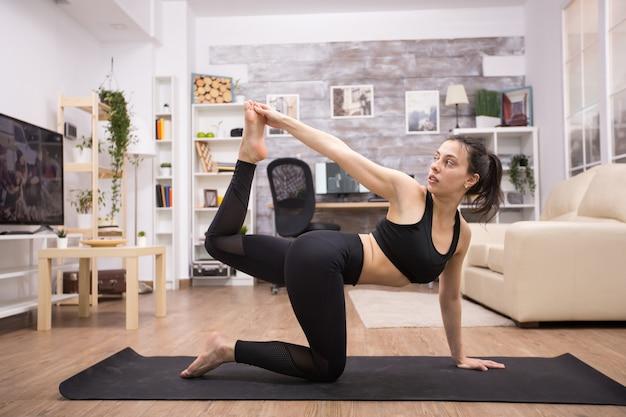 Donna caucasica che tiene il suo piede mentre fa una posizione yoga dell'equilibrio a casa.