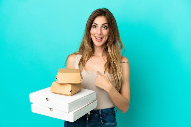 Donna caucasica che tiene pizze e hamburger isolati su sfondo blu con espressione facciale a sorpresa