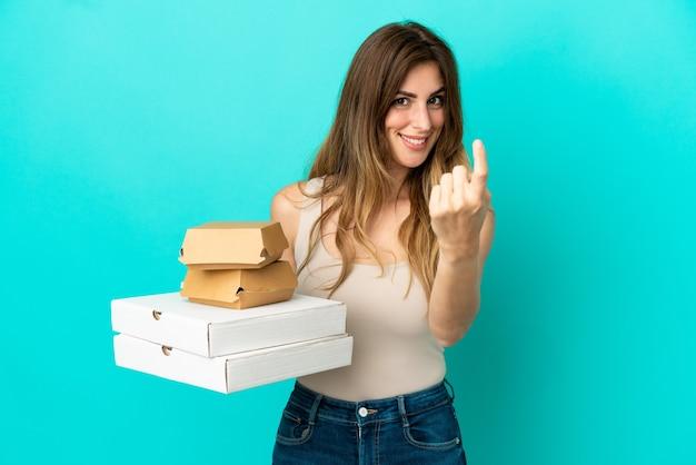 Donna caucasica che tiene pizze e hamburger isolati sulla parete blu che fa il gesto imminente