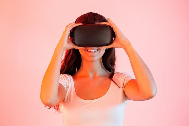 La donna caucasica che tiene la cuffia avricolare di realtà virtuale sulla testa di sentire con le mani su fondo rosa.