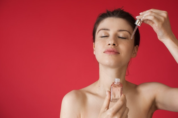 La donna caucasica sta applicando olio biologico sul viso in posa su una parete rossa dello studio con le spalle nude