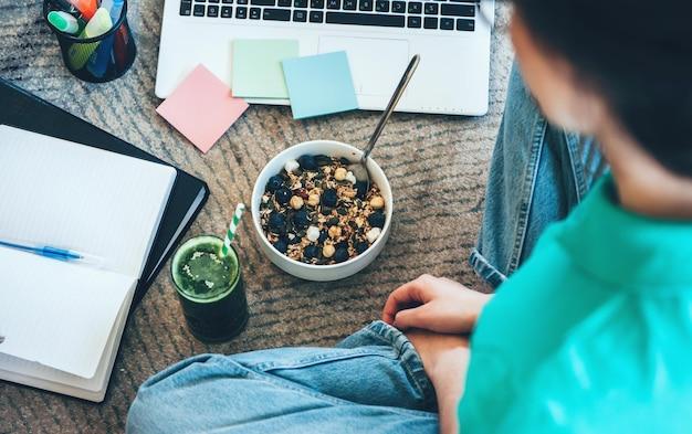 La donna caucasica sta facendo i compiti mentre mangia cereali con succo verde fresco sul pavimento
