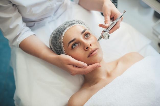 La donna caucasica sta avendo procedure di pulizia del viso presso il salone della stazione termale mentre indossa un berretto medico e si trova sul divano