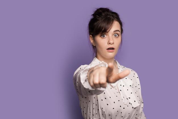 La donna caucasica sta indicando lo schermo con l'indice che osserva stupito la macchina fotografica su una parete viola dello studio