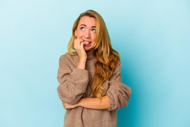 Donna caucasica isolata su sfondo blu che si morde le unghie, nervosa e molto ansiosa.
