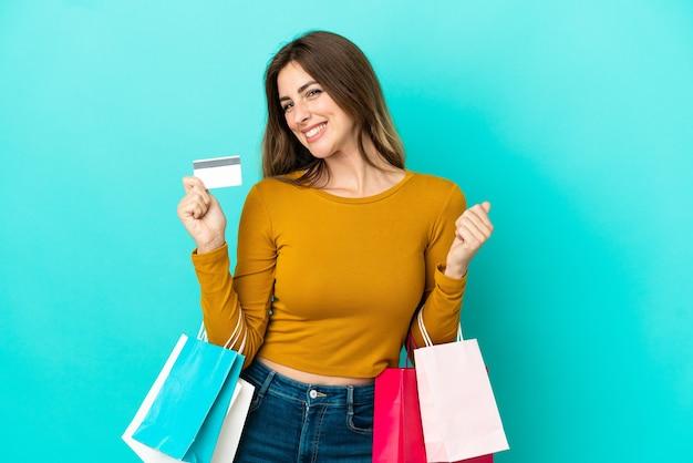 Donna caucasica isolata su fondo blu che tiene le borse della spesa e una carta di credito