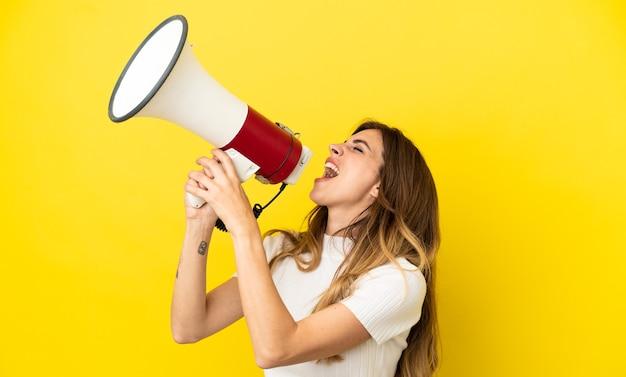 Donna caucasica isolata su sfondo giallo che grida attraverso un megafono per annunciare qualcosa in posizione laterale