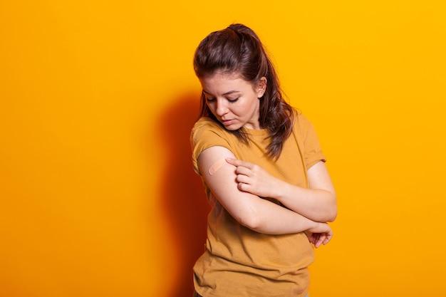 Donna caucasica che guarda un cerotto adesivo sul braccio