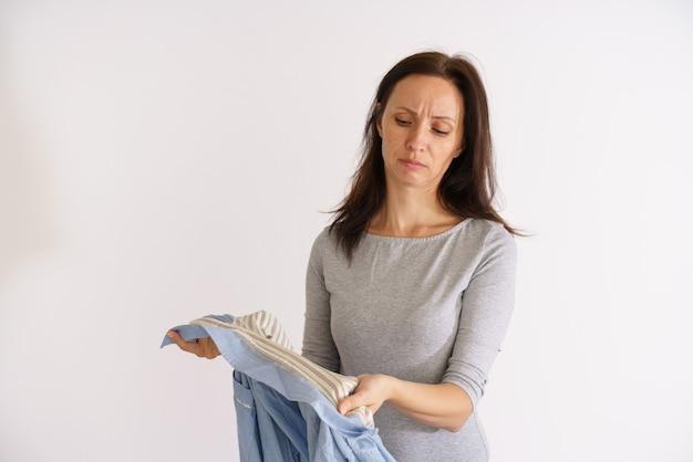 Donna caucasica che guarda una maglietta sporca e maleodorante su sfondo chiaro