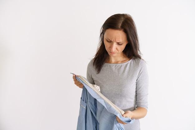 Donna caucasica che guarda una maglietta sporca e maleodorante sul muro chiaro light