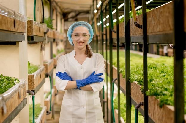 La donna caucasica osserva sulla coltivazione di insalata biologica in una fattoria idroponica