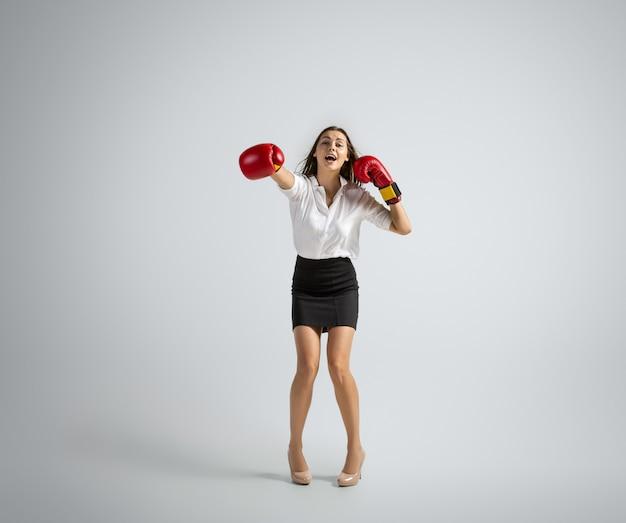 La donna caucasica nella boxe dei vestiti dell'ufficio isolata sul muro grigio
