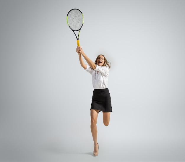 La donna caucasica in vestiti dell'ufficio gioca a tennis isolato sul muro grigio