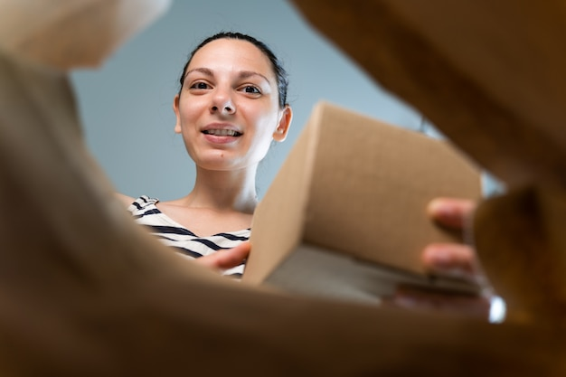 La donna caucasica apre il pacchetto di consegna della carta del mestiere con emozione felice.