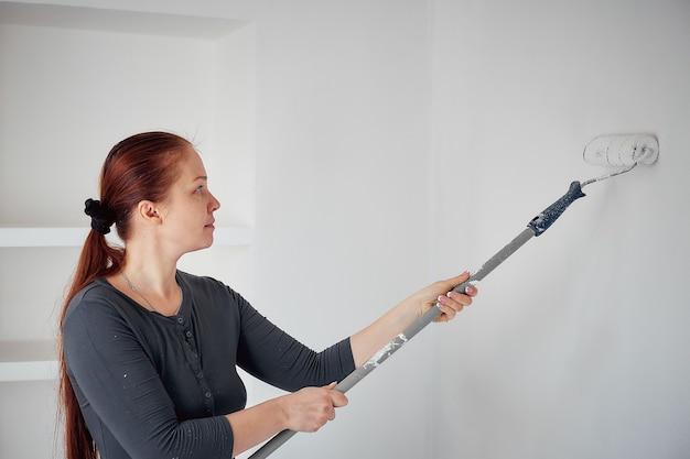 Donna caucasica che dipinge con un rullo le pareti dell'appartamento.