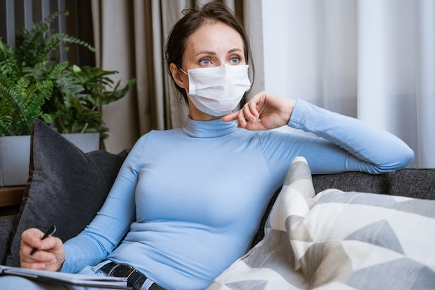 La donna caucasica in una maschera protettiva si siede sul divano con un taccuino in mano con uno sguardo pensieroso scrive
