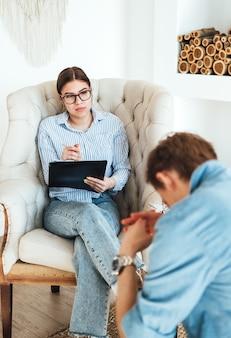 Psicologo della donna caucasica in occhiali seduto su una sedia che conduce una sessione di psicoterapia con un uomo arrabbiato paziente.