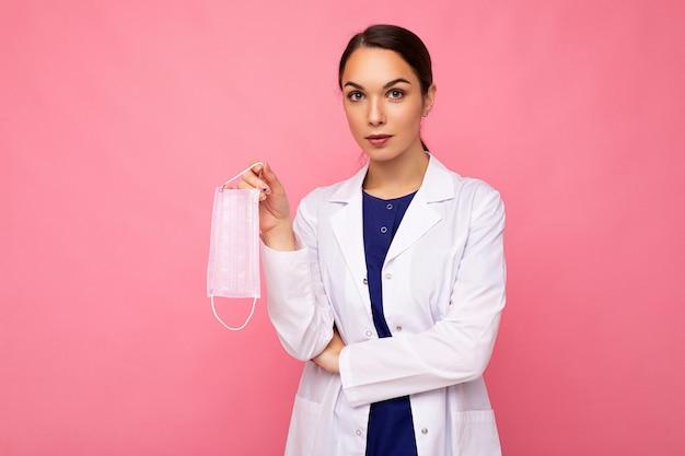 La donna caucasica che mostra la maschera per il viso di protezione isolata su sfondo rosa. concetto di coronavirus o covid-19.