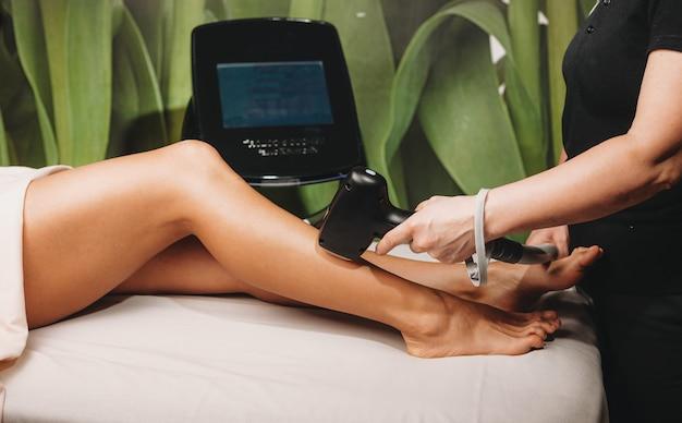 Donna caucasica che si siede sul divano della stazione termale con una procedura di epilazione delle gambe presso il centro benessere con apparecchiature moderne