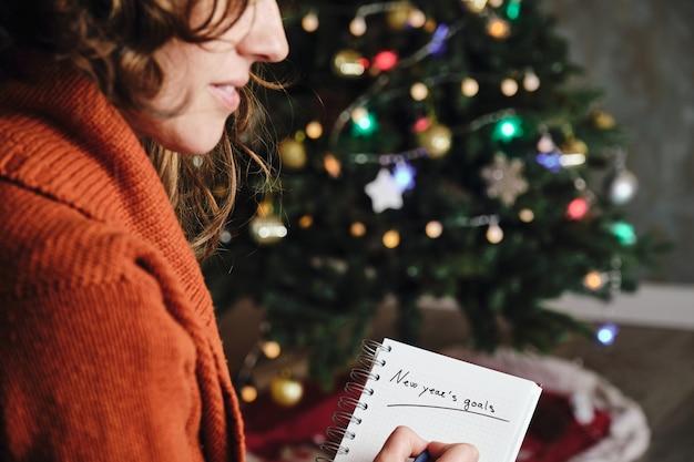 Donna caucasica sorridente con maglione arancione di profilo con taccuino degli obiettivi del nuovo anno in mano con albero di natale sfocato sullo sfondo