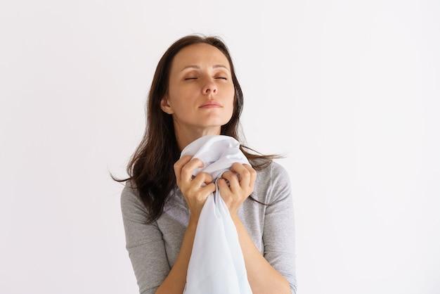 Donna caucasica che annusa camicia bianca pulita su sfondo chiaro light
