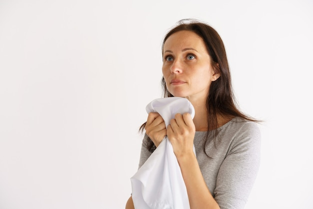 Donna caucasica che annusa una camicia bianca pulita sul muro chiaro light
