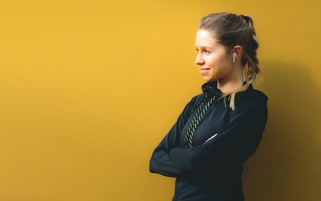 Donna caucasica in tuta sportiva con wireless headphonest su sfondo isolato