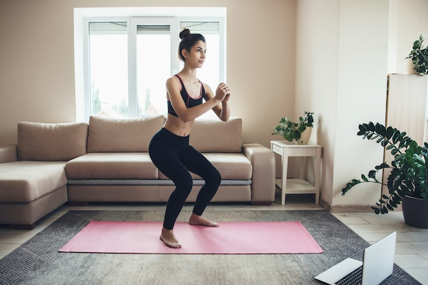 La donna caucasica in abbigliamento sportivo è accovacciata a casa durante la lezione di fitness online utilizzando un laptop