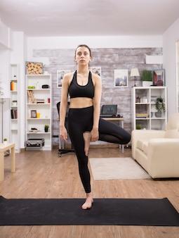 La donna caucasica in piedi su una gamba si è concentrata sulla sua buona postura. praticare lo yoga.