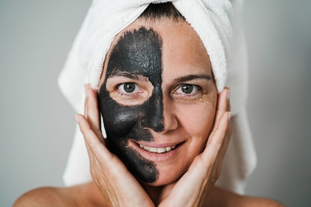 Donna caucasica che utilizza una maschera nera al carbone naturale per la cura della pelle - trattamento del corpo per un concetto di stile di vita sano - focus on eyes