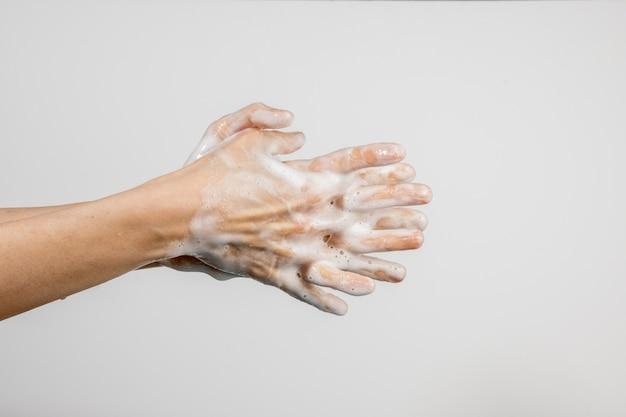 Donna caucasica che lava le sue mani isolate sulla parete bianca