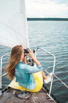 Donna caucasica che guarda binoculare sulla barca a vela