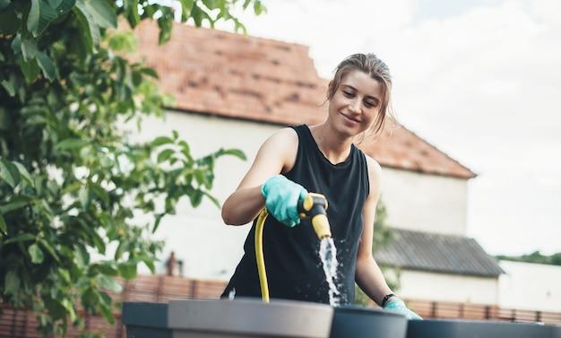 Donna caucasica che innaffia una pentola dopo aver piantato i fiori mentre sorride nel cortile