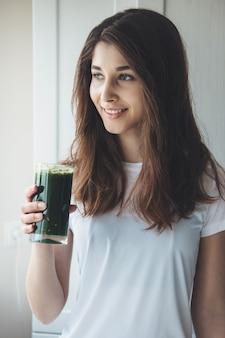 Donna caucasica con capelli neri che beve un bicchiere di succo di verdura fresca