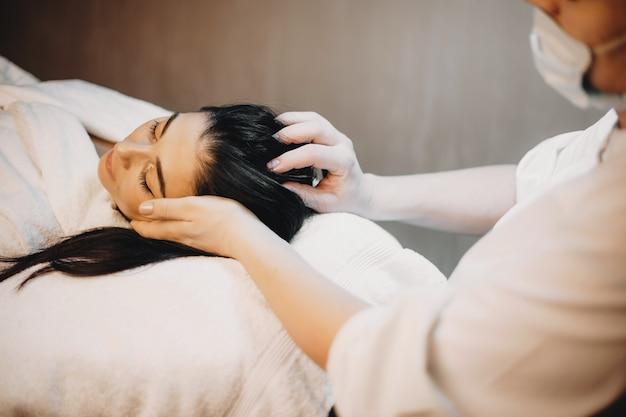 Donna caucasica con capelli neri che ha una procedura termale di massaggio alla testa presso il salone professionale