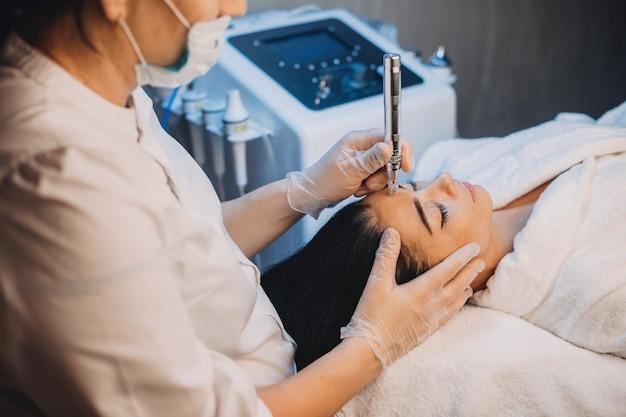 Donna caucasica con capelli neri sdraiata sul letto e avendo una procedura di cura della pelle del viso con apparato presso il salone spa